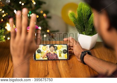 Shoulder Shot Of Young Man Busy In Video Call Or Chat On Mobile Phone On 2021 New Year Or Christmas