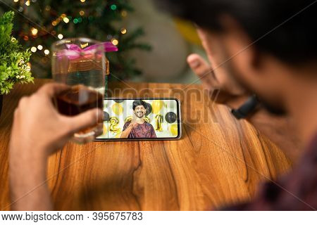 Shoulder Shot Of Young Man Partying By During New Year Or Christmas Celebration Video Call On Mobile