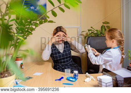 Little Girl Playing Pretends Like Paediatrician Doctor Examining A Patient In Comfortabe Medical Off