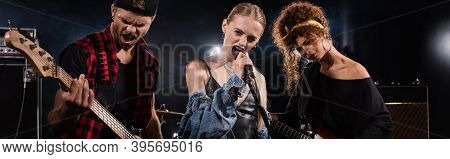 Female Vocalist Of Rock Band Singing Near Guitarists With Backlit On Background,