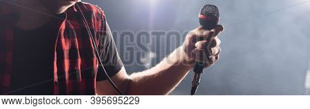 Cropped Of Vocalist Of Rock Band Holding Microphone On Blurred Background, Banner
