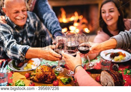 People Toasting Red Wine Glass Having Fun At Christmas Supper Reunion - Holiday Celebration Concept