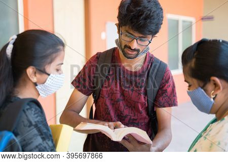 Group Of College Students In Medical Mask Discussing By Looking Into Book At College Campus Corridor