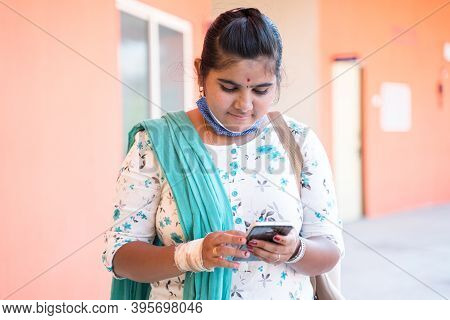 Young Girl With Medical Mask Worn Below The Chin Using Mobile At College Corridor - Concept Of Impro
