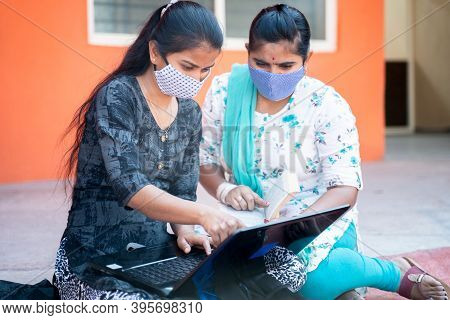 Two Young Girl College Students In Medical Mask Working Or Studying Project On Laptop At College - C