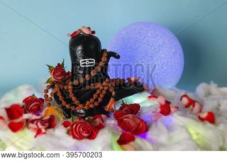 Black Handmade Shivalingam Figure In Divali Lights With Rudraksha Beads And Roses.