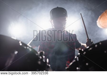 Rock Band Musician With Drumstick Playing Drums With Smoke And Backlit