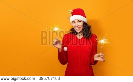 Young Happy Woman With Sparklers Celebrate And Laugh On Orange Background. New Year And Christmas Ce