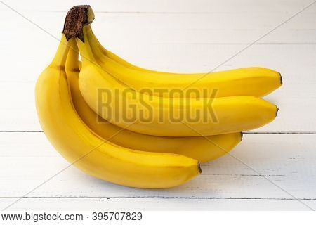 Ripe Yellow Bananas On White Wooden Table. Delicious Nutritious Fruit For Snack.