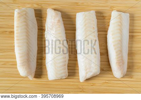 Fresh Iced Pieces Of Cod Fish Loins Or Fillets On Wooden Cutting Board. Top View.