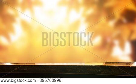 Thanksgiving Background Concept: Wooden Table And Blurred Autumn Background
