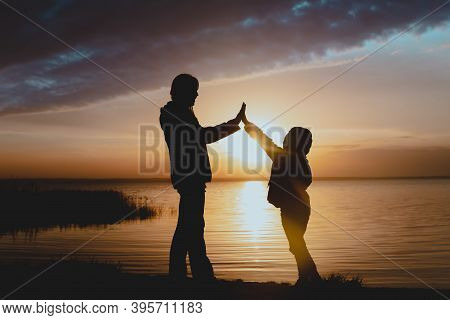 Happy Mother With Daughter High Five At Sunset On Lake