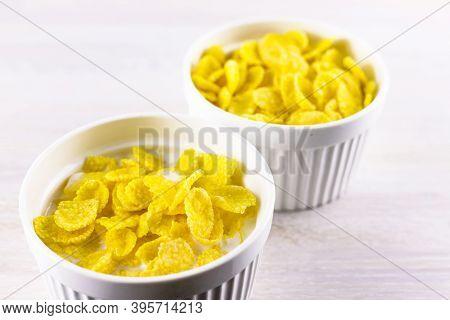 Corn Flakes In White Scandinavian Bowls Ramekin For Breakfast On White Wooden Table Background. Clos