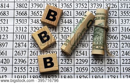 Bbb (better Business Bureau) - Acronym On Cubes On Paper Background With Numbers And Banknotes. Busi