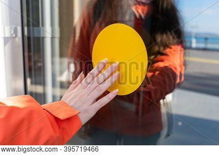 International Day Of The Blind. A Yellow Circle On The Door That A Blind Woman Touches. The Concept