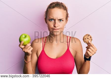 Beautiful caucasian woman holding green apple and cookie skeptic and nervous, frowning upset because of problem. negative person.