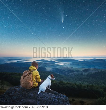 Alone tourist sitting on the edge of the cliff with white dog against the backdrop of an incredible mountains with starry night sky. Landscape photography
