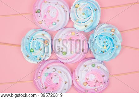 Colorful Meringue Cake Toppers On Pastel Pink Background. Trendy Banner With Or Meringue On Stick