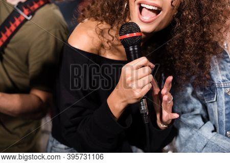 Cropped View Of Female Vocalist With Microphone Singing Near Rock Band Musicians On Blurred Backgrou
