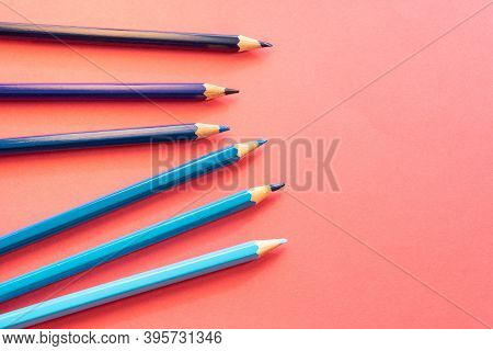 Blue Pencils Arranged Disorganized And Tilted Up On Pink Background