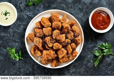 Crispy Fried Breaded Chicken Bites In Bowl Over Blue Stone Background. Tasty Chicken Nuggets. Top Vi