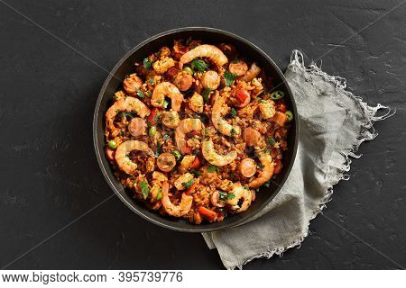 Creole Style Jambalaya With Chicken, Smoked Sausages And Vegetables In Frying Pan Over Black Stone B