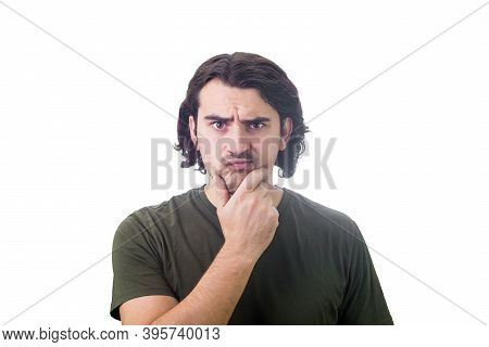Skeptical Young Man Thoughtful Looking To Camera, Keeps Hand Under Chin, Puzzled Suspicious Expressi