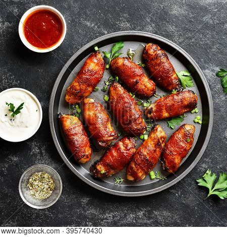 Bacon Wrapped Grilled Chicken Wings On Plate Over Dark Stone Background. Tasty Snack From Chicken Me