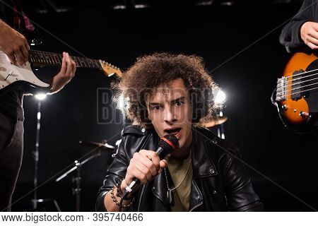 Kyiv, Ukraine - August 25, 2020: Curly Vocalist With Microphone Looking At Camera Near Musicians Wit