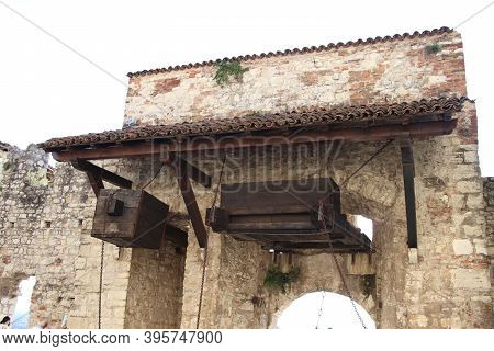 Stone Wall With Merlons And Drawbridge Gate Of Medieval Castle Of Brescia In North Italy