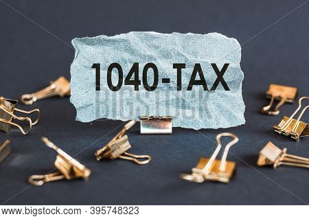 A Piece Of Blue Paper With Clips On A Gray Background With The Text - Tax 1040. Financial Concept. B