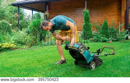 Electric Lawn Mower Breakdown. Malfunctioning Garden Tools. The Man Overturned The Grass Collector L