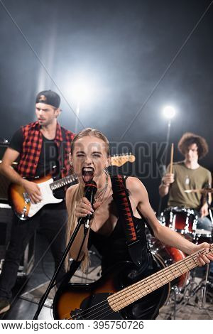 Kyiv, Ukraine - August 25, 2020: Female Vocalist Of Rock Band With Electric Guitar Screaming In Micr