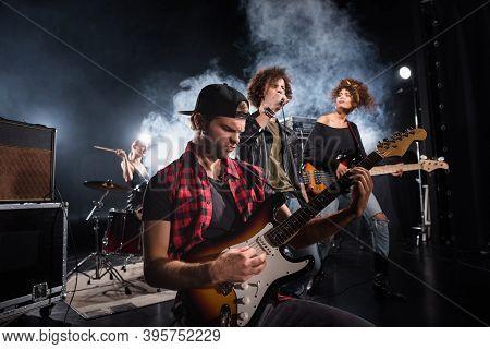 Kyiv, Ukraine - August 25, 2020: Rock Band Musician Playing Bass Guitar Sitting Near Curly Vocalist