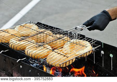 Hot Mouthwatering Toasted Hamburger Buns In The Grill Mesh.young Man Preparing Them On The Brazier.