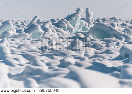 Transparent Blue Ice Floes Piled In Ice Hummocks Against A Blue Sky On A Sunny Day. Unusual Winter L