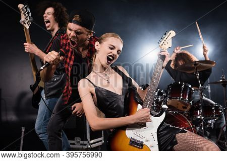 Kyiv, Ukraine - August 25, 2020: Blonde Woman Playing Electric Guitar While Shouting With Vocalist A