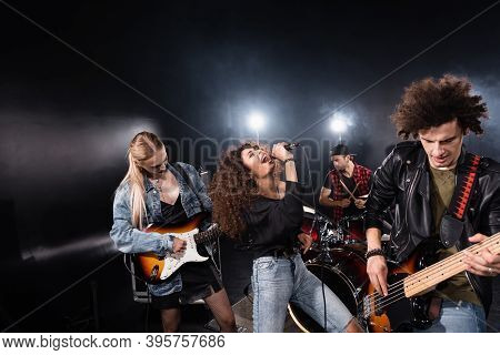 Kyiv, Ukraine - August 25, 2020: Curly Vocalist Of Rock Band Singing Standing Near Musicians Playing
