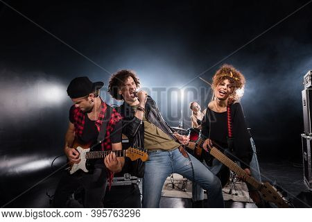 Kyiv, Ukraine - August 25, 2020: Curly Vocalist Singing In Microphone While Leaning On Guitarist Wit