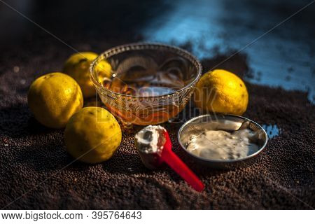 Mustard Seed Face Mask For Glowing Skin On Black Surface With Raw Fresh Lemons, Mustard Seeds, Yogur