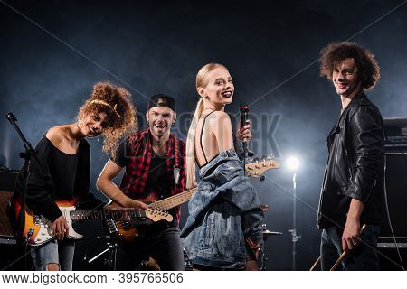 Kyiv, Ukraine - August 25, 2020: Happy Rock Band Vocalist Standing Near Curly Drummer And Smiling Gu