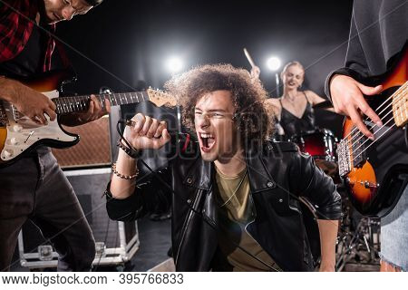 Kyiv, Ukraine - August 25, 2020: Curly Vocalist Shouting In Microphone While Sitting Near Guitarists