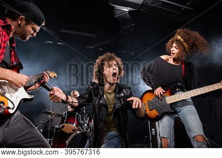 Kyiv, Ukraine - August 25, 2020: Curly Vocalist With Open Mouth Holding Microphone Near Guitar Strin