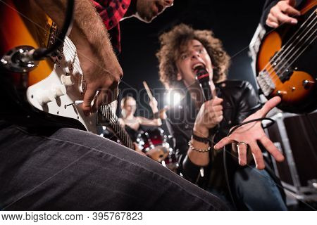 Kyiv, Ukraine - August 25, 2020: Low Angle View Of Vocalist Shouting In Microphone Near Guitarists W