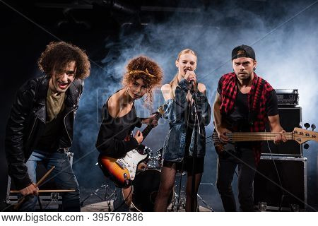 Kyiv, Ukraine - August 25, 2020: Female Vocalist Singing, While Standing Near Rock Band Members With