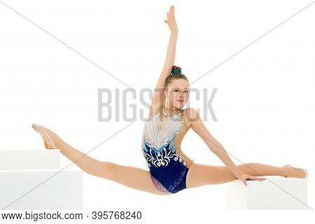 An Elegant Little Girl Gymnast In A Beautiful Sports Swimsuit Performs A Gymnastic Element, Twine, O