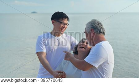 Asian Senior Love Couple With Son Travel On The Beach. Retirement Age Family Relaxing And Recreation