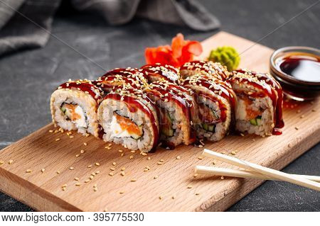 American Canada Sushi Rolls With Unagi And Salmon On The Wooden Board