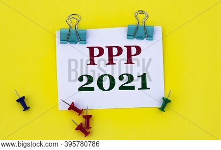 Ppp 2021 - Word On White Paper With Clips On Yellow Background With Buttons And Pencil. Technology A