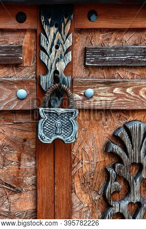 Closed Wooden Lock Door Security. A Wooden Carved Stylized Lock Hangs On A Wooden Decorated Door